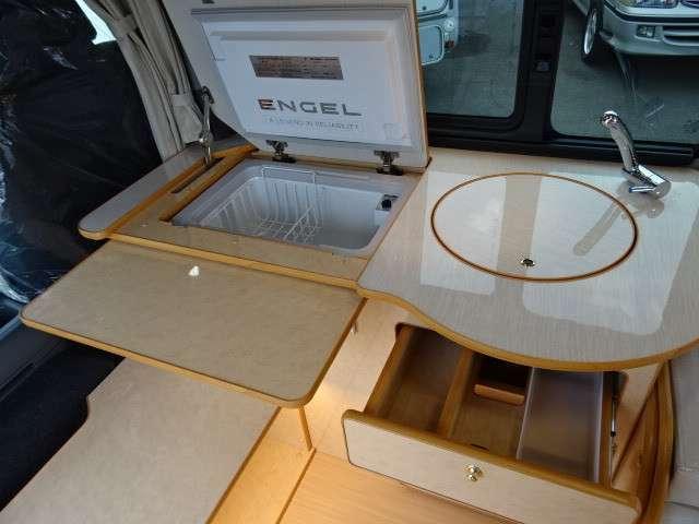深さと広さがある330mmサイズ丸型シンクを採用ギャレー部分を拡張できる、展開式テーブルを装備しています。運転席・助手席側からのアクセスが出来るようローボード家具を配置しています。