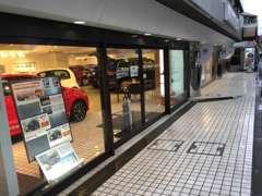 マンション1階が屋内展示場です。白いタイルの上が駐車スペースです。歩道を越して駐車してください。
