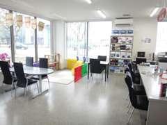 店内は、事務所兼商談コーナーの広いスペース。ガラス張りになって明るく、キッズスペースも完備しております。