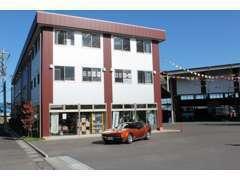 3階建ての白とエンジの建物1階が受付フロアーになります。