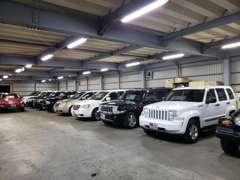 【大型ガレージ】屋内展示場にも所狭しと在庫車を展示しております。国道16号線外回り沿いです。豊春駅より無料送迎致します。