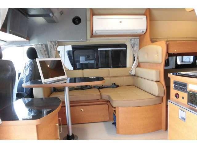 ダイネット廻り シートはレザー調のベージュ系シートになります。オプションの家庭用ルームクーラーはインバーター2000Wとセットで350000円(税別)です。後席用ワイヤレス液晶TVも標準で付いています。