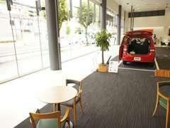 お客様にゆったりとした気分で車選びをして頂けるよう、商談スペースは天井を高くし太陽光溢れさせて開放感を演出しております。