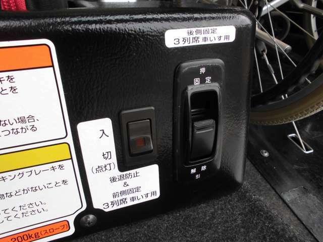 後ろ側車いす用の、後退防止ベルトと電動固定装置のスイッチ。