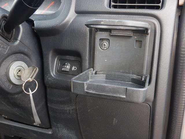 【運転席側インパネ】ヘッドライトの高さを調節するライトレベライザーと開閉式のカップホルダーです。