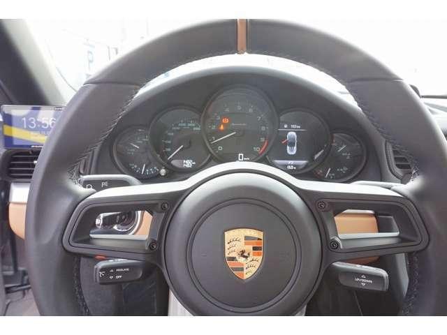 シンプルなデザインのコックピット ステアリングホイールに走行モードのセレクターやインフォテインメントシステムのスイッチは備わらない。ハンドルパターン表示はゴールドになります。