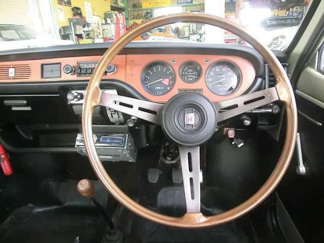 ウッド調パネル、3本スポークのスポーティなステアリングが軽自動車らしからぬ高級感を演出するインパネ。