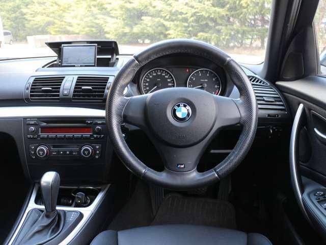116iMスポーツの運転席まわり。角度調整が細かく設定できる固めのスポーツシートや太めのハンドルグリップが特徴的なMエンブレム付き革巻きステアリング
