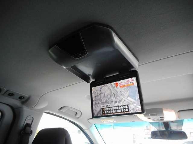 このお車につきましては、フリップダウンモニターが標準装備となります。HDDナビゲーションと連動しておりますが、運転席でナビゲーションを見ていてもフリップダウンモニターではテレビやDVDが楽しめます。