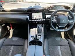 ピアノフィニッシュのハイセンターコンソールとカーボン調のダッシュボードに囲まれたi-Cockpit