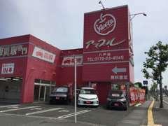 アップル八戸店は、国道45号線沿い新井田川手前にある赤い建物で、大きなりんごのマークが特徴のお店です。