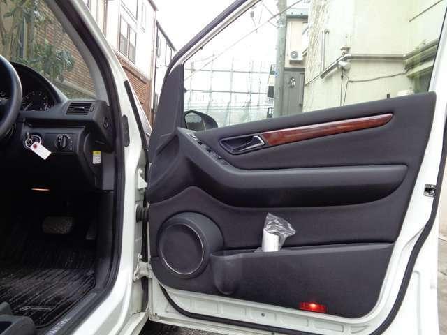 インテリアと同色のスクエアーデザインのオフブラックドアモールにはカップホルダーやフロントスピーカーにウッドデザインパネルを装備。清潔感が高く清楚な印象の移動空間でスクエアーなメルセデスデザイン車輌です