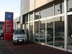 当店は札幌市の石狩街道沿いにございます。黒とグレーのツートンカラーの建物で赤い看板が目印です。