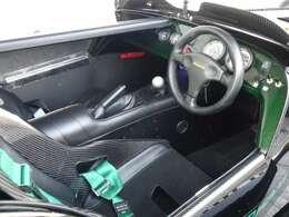 右側の運転席のみに限定されるキャビンは、シートにカーボンファイバー製のスポーツシートを使い、カーボンファイバー製ダッシュボード、アルマイト処理したシフトノブ、タカタ製の4点式シートベルトを採用する。