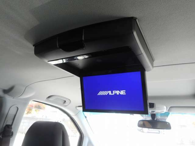 このお車につきましては、フリップダウンモニターも装備されております。HDDナビゲーションと連動しておりますが、運転席でナビゲーションを見ていてもフリップダウンモニターではテレビやDVDが楽しめます。