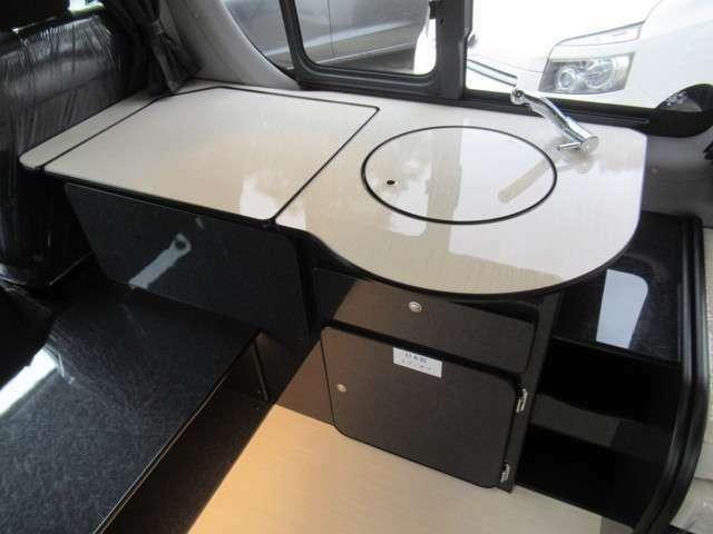 深さと広さがある330mmサイズ丸型シンクを採用。(見た目も美しい専用蓋付き)ギャレー部分を拡張できる、展開式テーブルを装備しています。運転席・助手席側からのアクセスが出来るようローボード家具を配置。